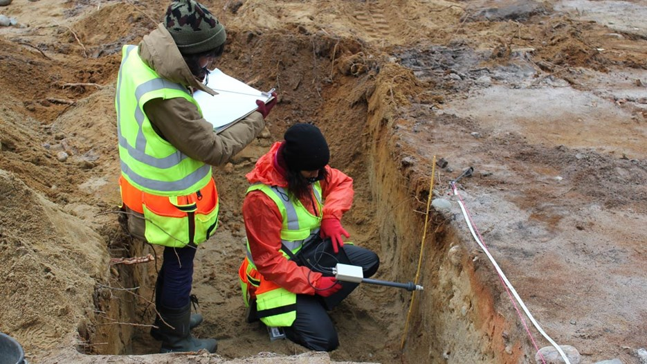 Two students of archaeology investigates an earli metal production site using magnetic suceptibility