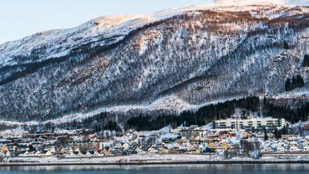 The small Norwegian city Tromsö, seen from below a snowy mountainside.