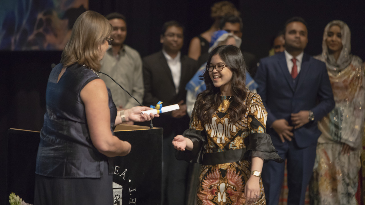 Photo of a student receiving a congratulatory scrole on stage at the Graduation Ceremony.
