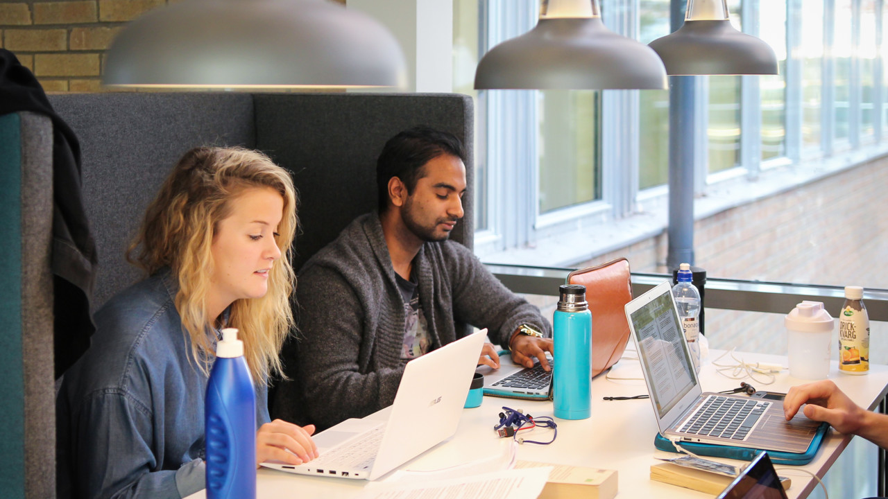 Students with laptops studiing at a table at Umeå University