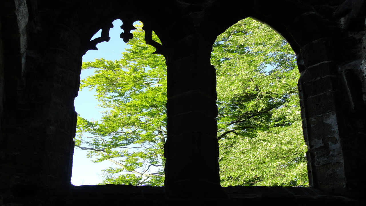 Two church windows opeing up towards green trees outside