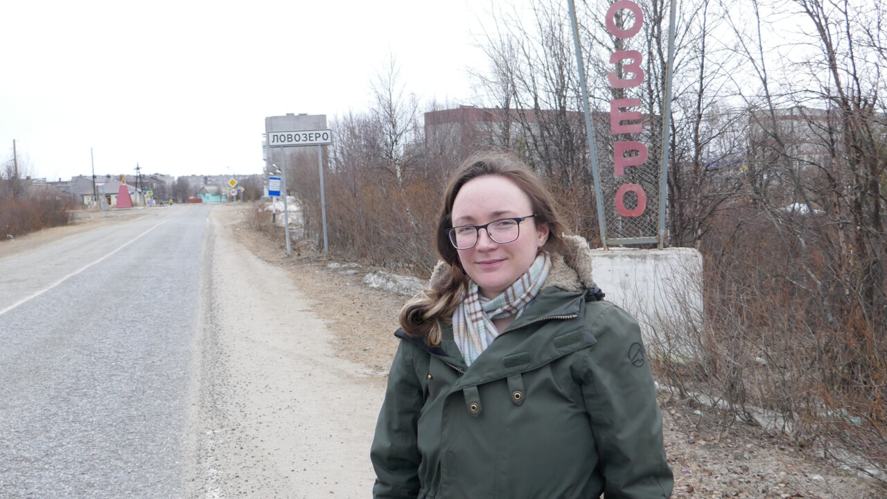 Woman stands by road, in front of roadsigns with Cyrillic text.