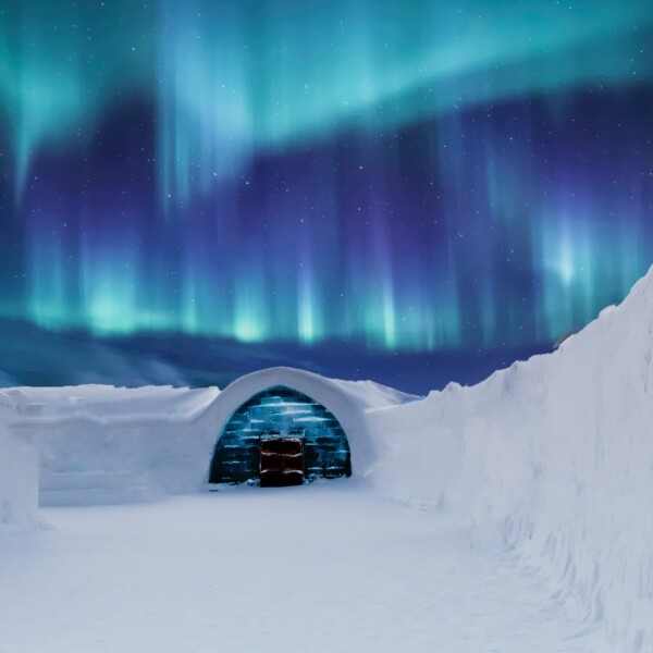 A snow building with a wooden door, high snow edges and a dark blue sky with northern lights.