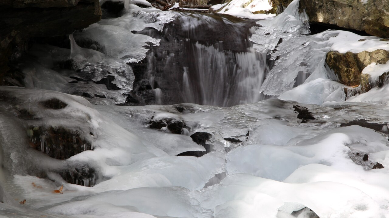 Stream in snowy landscape with rocks and ice and water rushing