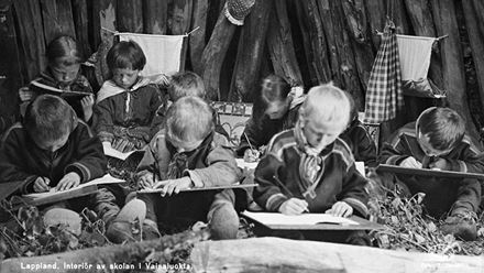 Historical black and white interior photo of several Sami children attending nomadic Sámi school in Vaisaluokta, Norrbotten.