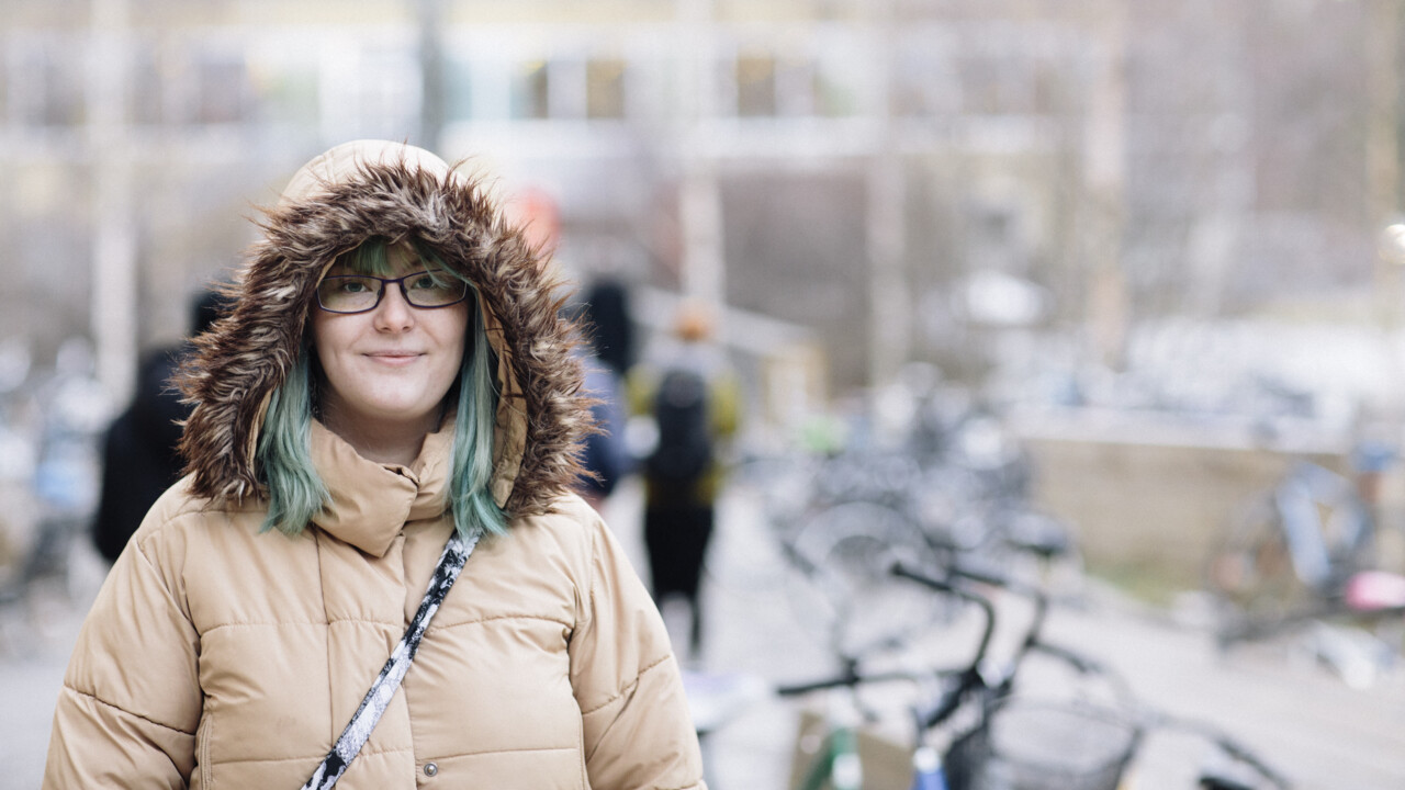 Photo of a student outside of Lindellhallen, dressed in winter clothes.