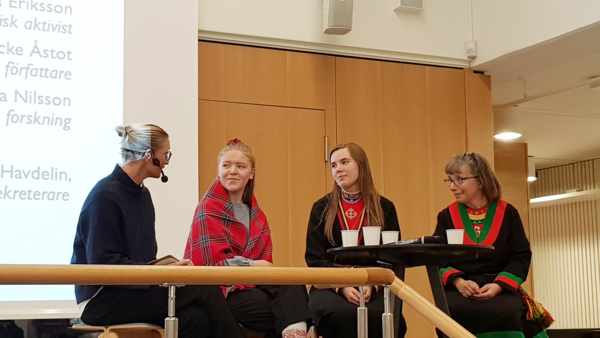 Four women seated in a panel discussion, with three clad in Sami clothes